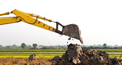 excavator backhoe arm with a bucket is working in the digging a soil to adjust the postharvest areas in the rice fields. agriculture machinery fo the modern agriculture industry.