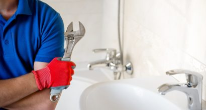 plumber with wrench standing in bathroom